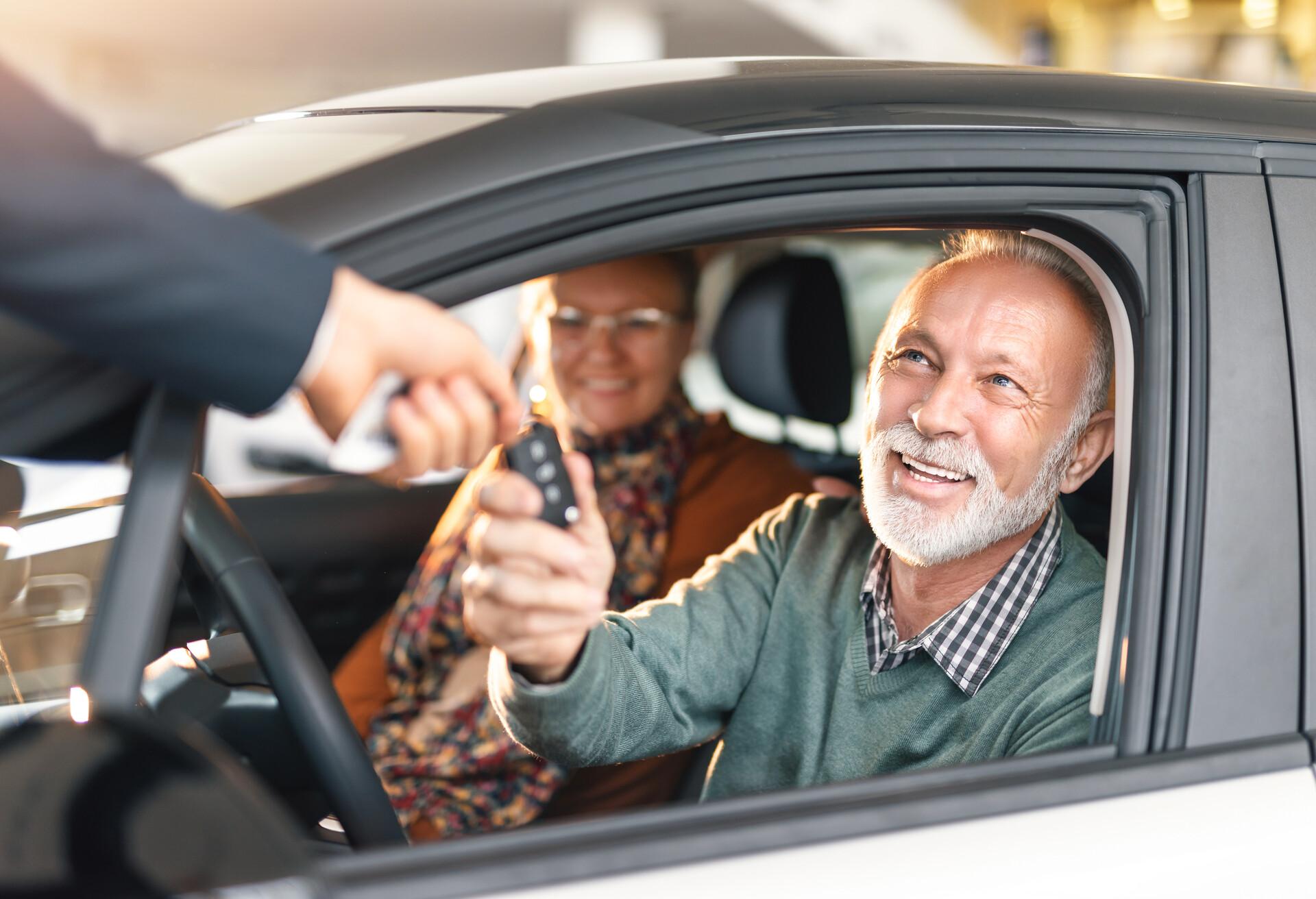 An elderly couple driving a hire car.