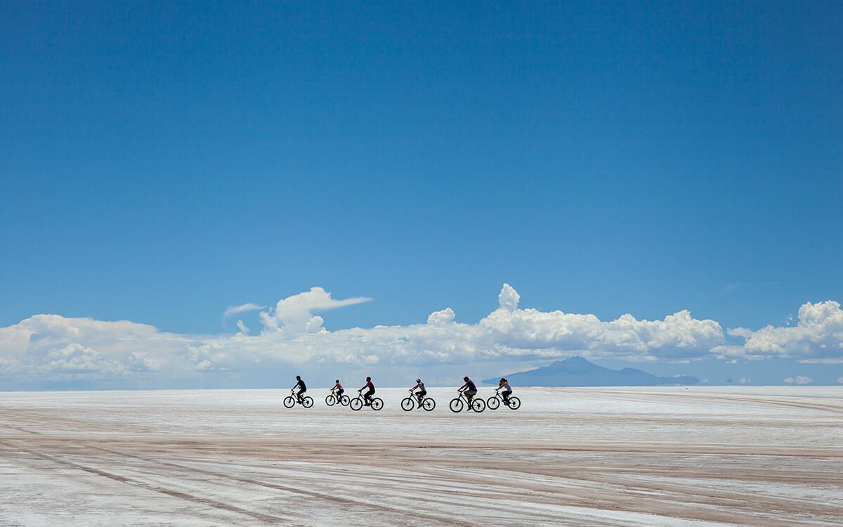 people cycling across salt flats