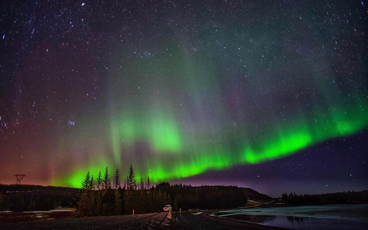 Watch the Northern Lights brighten up the dark landscape in Tromsø, Norway